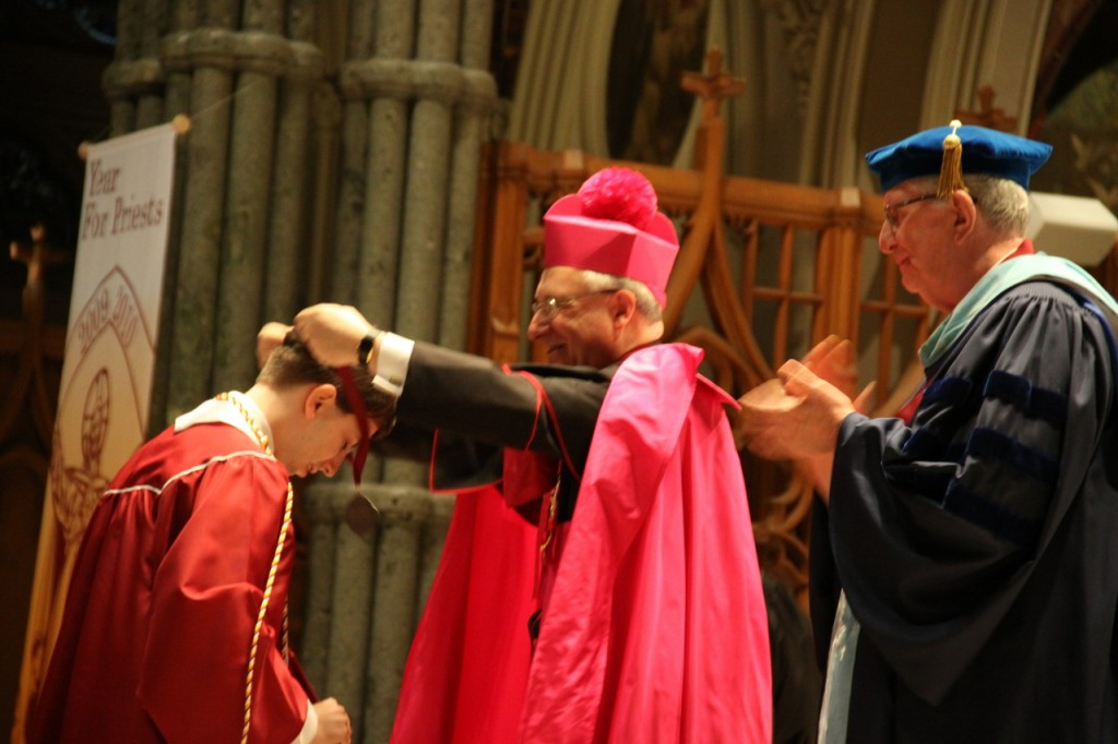 WELL-DESERVED: Bishop Robert C. Evans presents Michael H. Danielewicz with an honors medal as Brother Michael McKenery applauds the achievement.