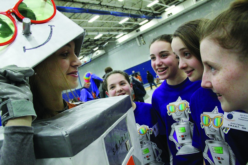 MAKING ALL THE RIGHT MOVES: From left, eleventh-grader Jesse Grasso, left, draws a crowd of her St. Mary Academy Bay View teammates, including seventh-graders Megan Nadeau, Allie Cross and Jackie Capuano, and fifth-grader Blaine Lynch-Gadaleta as she travels the Roger Williams University gymnasium as the team's mascot. The St. Mary Academy Robotics Team won first place in last weekend's First Lego League competition at Roger Williams University. They will travel to St. Louis, Mo., in April to compete in the First Lego League World Festival.
