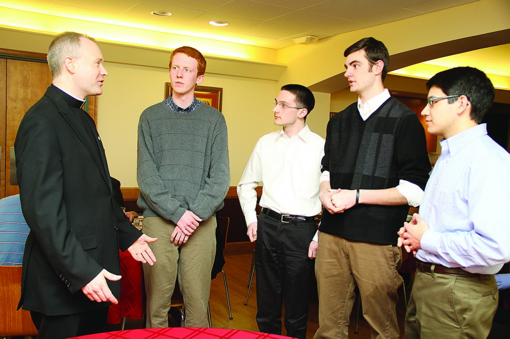 NEW MENTOR: Father Christopher Mahar greets a group of seminarians during a visit to Our Lady of  Providence Seminary Tuesday. With him, from left are seminarians Craig Cooley, Phillip Dufour, Mark Dushel  and Daniel Sousa. Father Mahar will become the rector of the seminary on July 1.