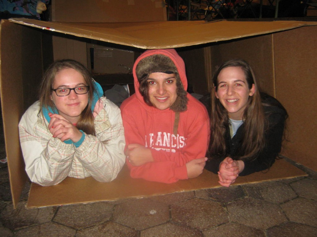 HUDDLED TOGETHER: From left to right, Prout School, Wakefield students Sarah Iselin, Chandler Dupre and Tory Kern see what it is like to sleep in a cardboard box as they prepare to spend the night on the grounds of the Cathedral of SS. Peter and Paul, Providence for the 'Sleep Out.' The event offered the students a closer look at issues of homelessness.