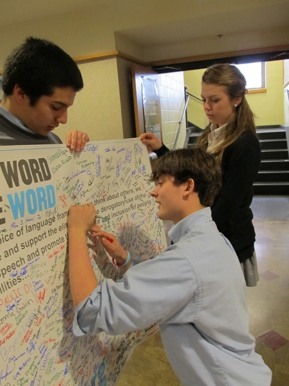 SHOWING SUPPORT: Jeffrey Jaquith (center) president of the La Salle chapter of Best Buddies, signs a petition to not use negative labels that hurt people with physical and intellectual challenges. Holding the petition are Jonathan Estrada and Jessica Desrosiers.