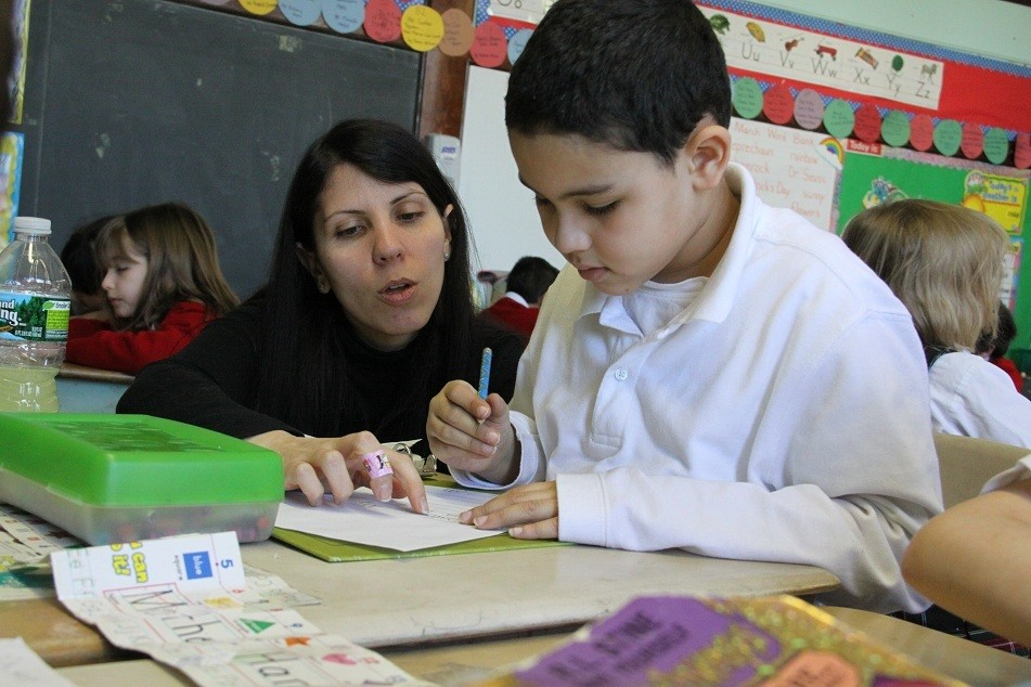HELPING HAND: First grade teacher Dayna Hudick helps Jaden Perry with a difficult math problem. Thanks to a generous bequest, St. Elizabeth Ann Seton Academy will be able to offer increased tuition scholarship help to families demonstrating the greatest financial need.
