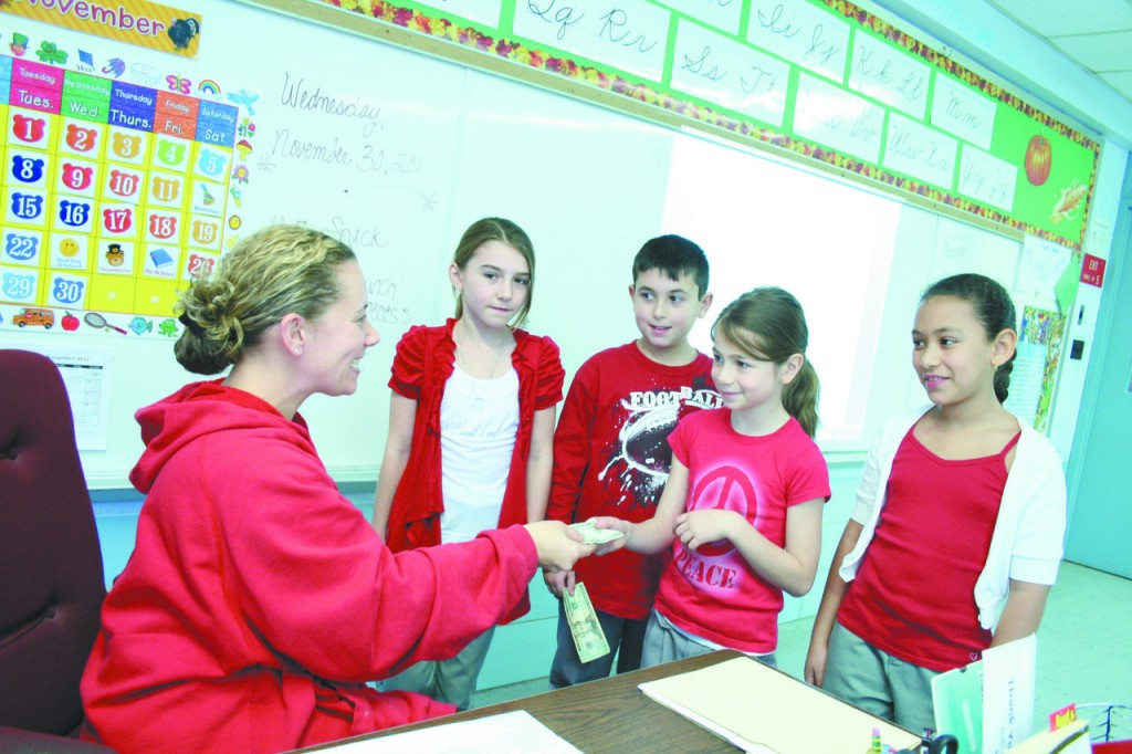 """A GIFT OF WARMTH: A Gift of warmth: From left to right, Grade 3 students at St. Rocco School in Johnston, Morgan Riel, Louis Kogut, Mia Mollicone, and Maria Fabal hand in their """"Keep the Heat On"""" donation to their teacher, Mrs. Jennifer Sweet. Students throughout the school were allowed to dress in red after making a donation to the program which helps provide heating assistance to those who have exhausted all other public and private means of assistance. The school raised $250 for """"Keep the Heat On."""""""
