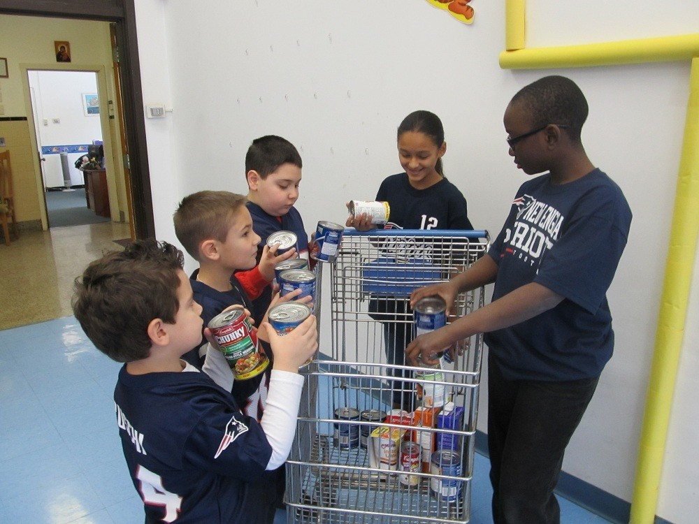 SOUPER BOWL: St. Thomas School, Providence, students (from left) Landon Faucher, Joshua Kacharo, Giorgio Angelino, Stephanie Cuervo and Samy Diouf load a shopping cart with cans of soup to benefit the parish food pantry.