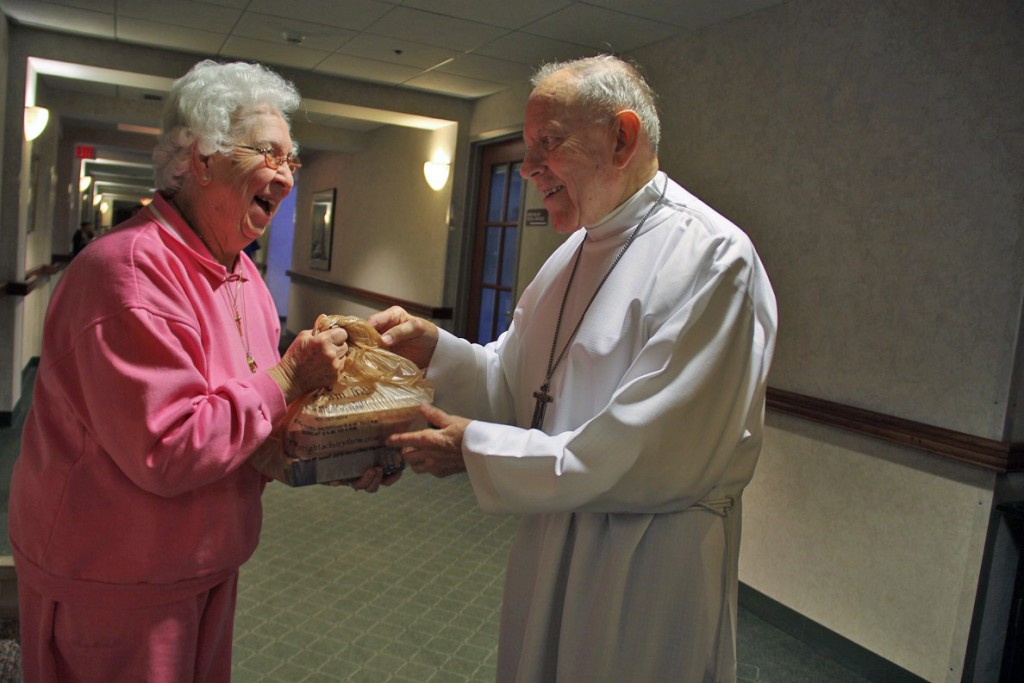 JOYFUL MEETING: Elaine Sauro shares some baked goods with Bishop Louis E. Gelineau following morning Mass at Saint Antoine Community, where he serves as chaplain, and also now resides.