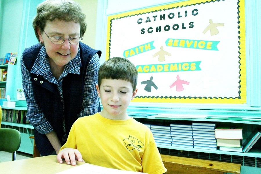 HONORED: Second grade teacher Heidi Cozzolino and Michael Esposito look over a play written by one of her students.?The St. Pius X teacher recently received the 2012 National Catholic?Educational Association Distinguished Teacher Award. Cozzolino will be representing all of the New England dioceses during the spring convention and awards banquet. ?Beloved by the St. Pius X community, Cozzolino shares the faith in every aspect of her mission to educate her students.