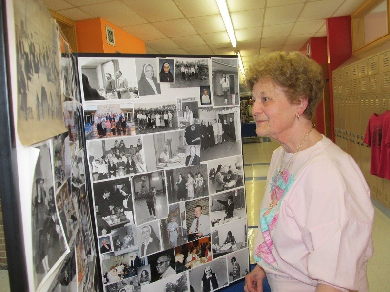 ACKNOWLEDGING HISTORY: Linda Fogarty, a parishioner of St. Margaret Church, East Providence, views pictures depicting Our Lady of Fatima's colorful history. She noted that the school provided her two grandchildren, Erin and Patrick Fogarty, with a values-based education that will serve them well throughout their lives.