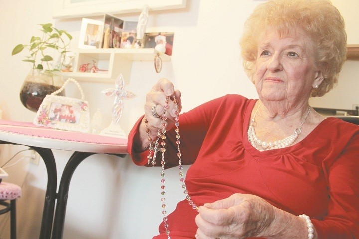THE POWER OF PRAYER: Nancy Davey practices her daily devotion, praying the rosary in her apartment at Brook Village in North Providence. Although dismayed that the complaint of a fellow resident prompted the company managing the complex to ask her rosary group to refrain from praying for a while in the facility's common area, she was never undeterred in her faith. She invited the other two members of the group to instead hold their weekly Monday afternoon prayer sessions in her apartment.
