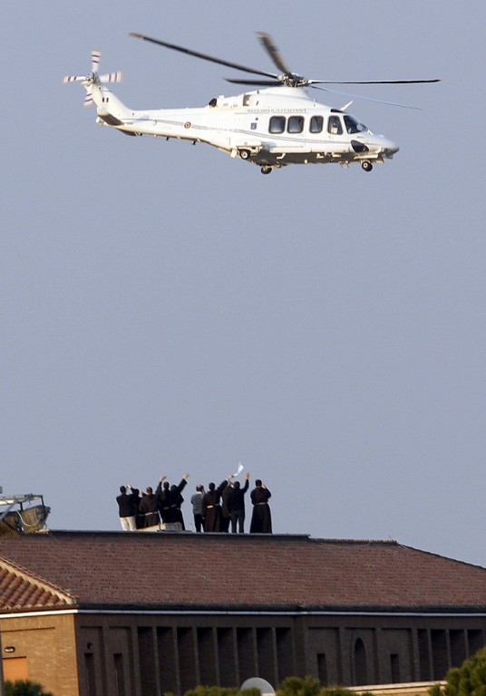 POPE EMERITUS: Clergy and Vatican workers wave from a rooftop as the helicopter carrying Pope Benedict XVI leaves the Vatican on its way to the papal summer residence at Castel Gandolfo, Italy, Feb. 28.