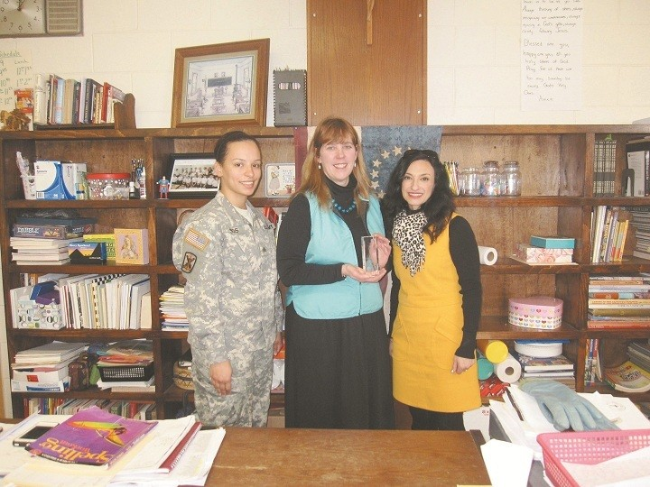 FAITH AND SERVICE: Sgt. Diana Jimos, left, and Lori Hart, right a Yellow Ribbon Specialist with the Rhode Island Air National Guard, present Collette Maynard, a grade 6 teacher at Father John V. Doyle School, Coventry with the Minuteman Award in appreciation for her service to the National Guard. Maynard has routinely enlisted the help of her middle school students to prepare cards, letters and other special acknowledgements to show support for members of the Guard as they serve their country. The Minuteman Award recognizes exceptional achievement, a patriotic act, highly distinguished service or an outstanding contribution to a military organization, community, state, nation, as well as to the National Guard Association. During the Year of Faith, Catholics are reminded of their call to prayer and service and are encouraged to help others live their lives with faith, hope and love.