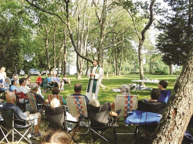 "BEAUTY OF CREATION: Father Przemyslaw ""Shemek"" Lepak, new pastor of St. Theresa and St. Christopher Parishes in Tiverton, celebrates a 'Mass Under the Trees' at the annual joint parish picnic at Colt State Park in Bristol.  Despite the threat of rain, parishioners continued to enjoy the picnic that was coordinated by the Men's Guild of St. Christopher Parish. The parish united in faith during the special celebration which fosters a close bond between the two faith communities. During the Year of Faith, Catholics are encouraged to come together as parish neighbors, to work together to spread the Gospel and support each other as spiritual brothers and sisters."
