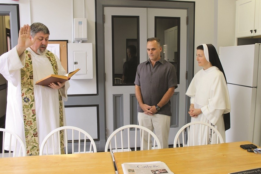 MANY BLESSINGS: Father Augustine Judd, O.P., pastor of St. Pius V Church, blesses the remodeled lunch room at the parish school Friday, August 23. Richard Pezzuco, co-owner of Pezzuco Construction Co., the benefactor who funded and organized the work, and Principal Sister Mary Veronica, O.P., join in prayer.
