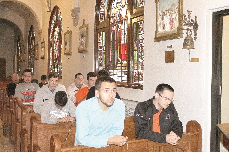 PRAYING TOGETHER: Members of the Oratory for College-Age Men gather to pray the rosary inside Our Lady of Mount Carmel Church, Bristol, as they reflect on a talk about grace-filled ways Catholics can demonstrate their power. Joshua Cordeiro, front row, left, a recent graduate of Mount Hope High School who will soon attend Community College of Rhode Island, and Phillip Dufour, a student at Providence College and a seminarian at Our Lady of Providence Seminary, join the group in praying the rosary.