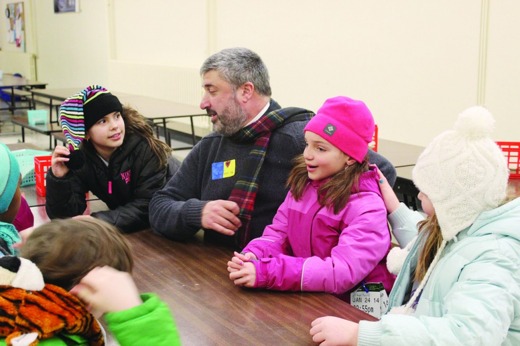 STAYING WARM: St. Cecilia students also raised funds when they donned scarfs, gloves and hats in class last month as a reminder that not everyone has the means to warm their homes when it?s cold outside. Father Michael Sisco, pastor of Blessed John Paul II Parish, who is sitting with fourth graders Morgan McCann, 9, Lexi Scott, 9, and Katie Grogen, 9, said, ?We always try to make the kids aware of social issues and the need to help the poor.?