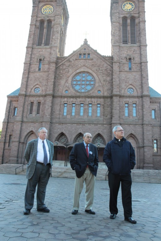 "Bishop Thomas J. Tobin leads Providence mayoral candidates Dr. Dan Harrop, left, and Vincent ""Buddy"" Cianci Jr., center, on a tour of the deteriorating conditions of the city's Cathedral Square on Monday."