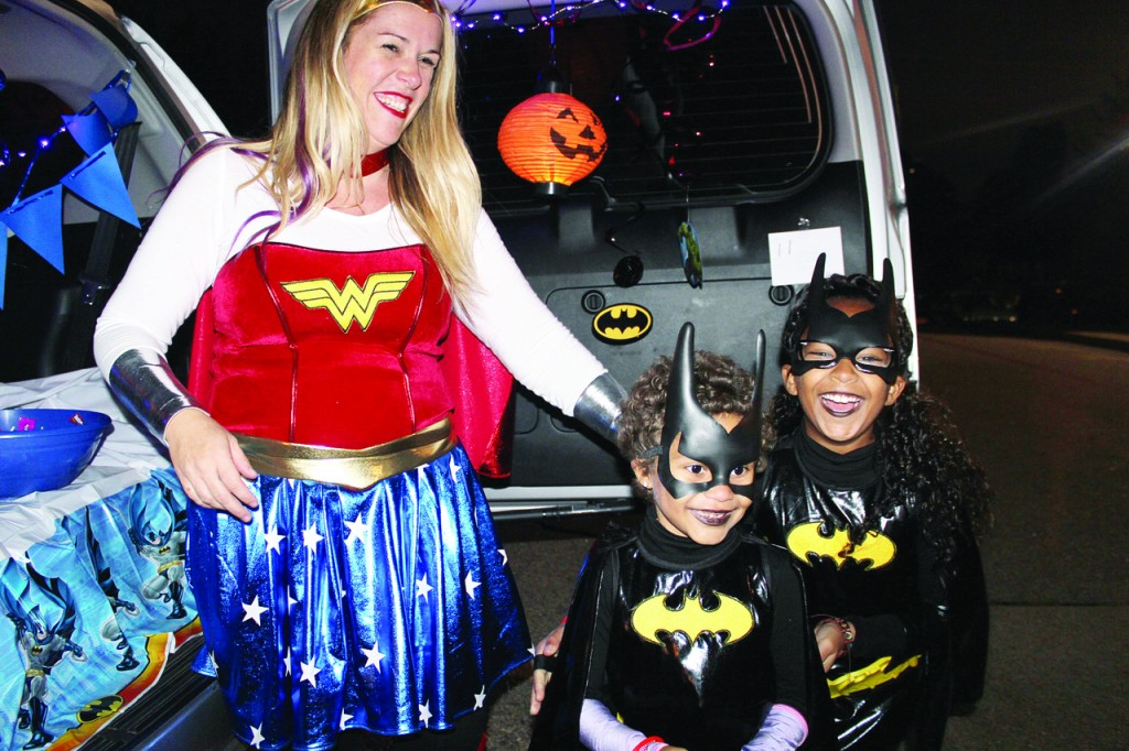 "GRINS AND GIGGLES: Dressed as Wonder Woman, Erin Devine passes out candy to her daughter, Amaya, 6, (left) a kindergartner at Cranston's St. Mary School, and her friend, Cassidy Cardoso, 9. Despite recent school threats, Devine thinks it's important ""to move on,"" and enjoy activities such as the school ""Trunk or Treat"" event, which was held at St. Mary Friday night."