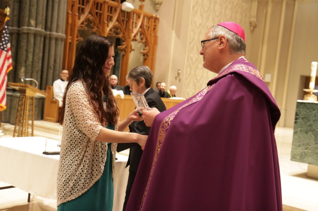 "Emily Cuellar, a freshman studying psychology and religious studies at Salve Regina University, receives from Bishop Thomas J. Tobin the St. Timothy Award in recognition of her service inspiring young people to follow their faith at the Rejoice in Hope Youth Center. ""Emily is on fire with her faith. She is a dedicated follower and servant of Jesus, giving witness to her faith and her love for God in all she does,"" her nominator for the award wrote of Emily. Other winners in the category were Daniel Arteaga, Kyle Aubin, Thomas Desmarais, Lauren King, Aaron O?Brien Mackisey, Jordan Robitaille, Kara Tracy, Ashley van Orsouw and David Zuleta."