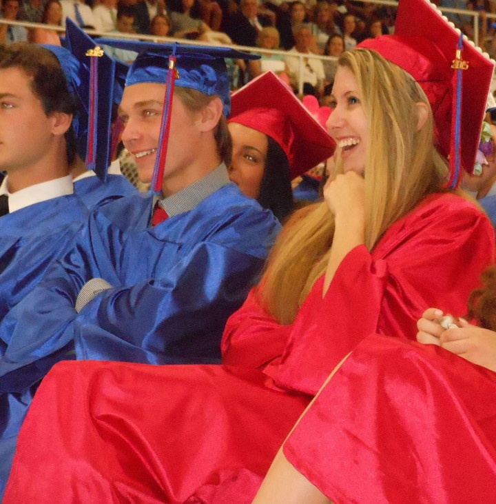HAPPY OCCASION: Graduates Jake Bacon of Cumberland and Brianna Arnold of Bellingham, Mass. laugh during salutatorian Jacob Haddad's address.