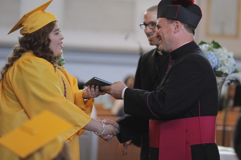Aida M. Buccio, who will attend Community College of Rhode Island, receives her diploma from Msgr. Albert A. Kenney, diocesan Vicar General and Moderator of the Curia, as Father James Ruggieri, pastor of St. Patrick Parish, looks on.