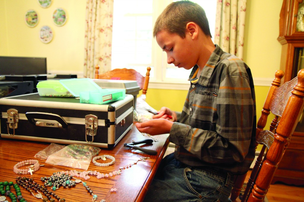 MASTER OF HIS CRAFT: 13-year-old Daniel Wilkins demonstrates how he uses a wire crimper to attach precious stones to a length of chain for one of his handmade rosaries.