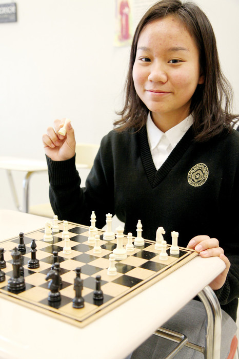 STAYING INVOLVED: Molly Mo, a sophomore at St. Raphael Academy and international student from China, plays a game of chess, a skill she practices often at home with her host-father. Like many of her fellow international students, Mo is involved with numerous extracurricular activities, including chess club, math team, Future Business Leaders of America and volunteering at the local food pantry.