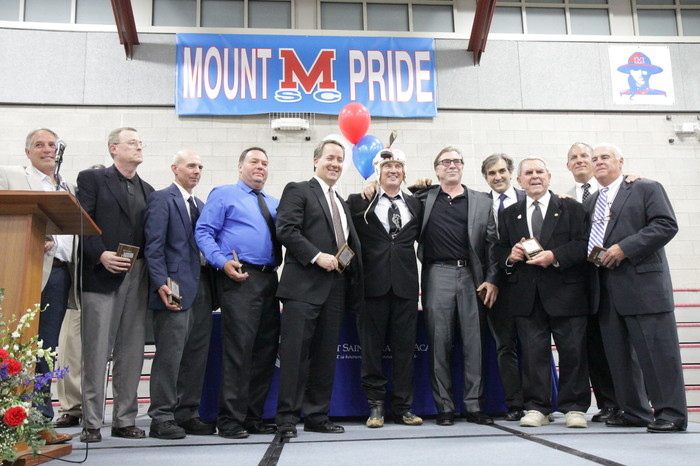Members of the 1978 boy's hockey team pose for a photo at the third biannual Mount St. Charles Academy Athletic Hall of Fame induction ceremony. The 1978 team, under the leadership of longtime hockey Coach Bill Belisle (third from right), won the first in a record series of 26 consecutive state championship titles.