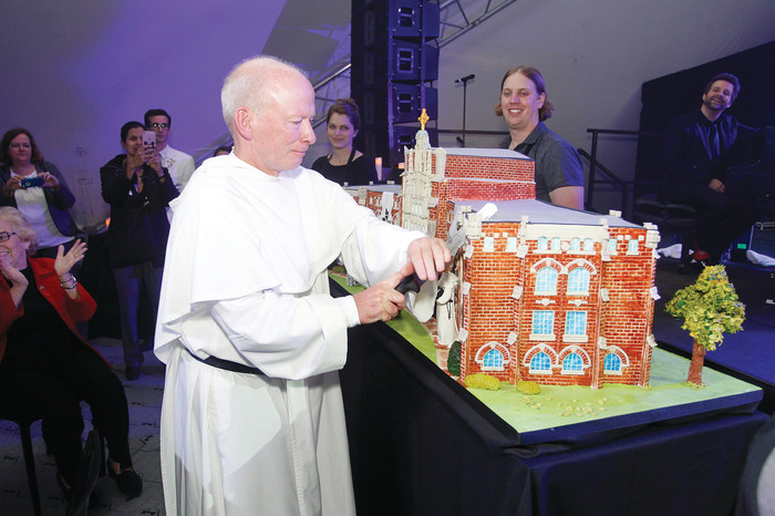 Father Brian Shanley cuts the Centennial cake at Saturday's St. Dominic Weekend celebration. The finished cake served 800 guests and included more than 100 windows, four fondant figures and 12 layers at its highest point.