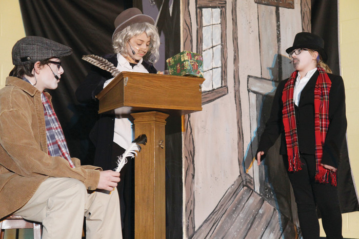 Sixth grader Isabella Rocheleau, playing a charity collector, addresses eighth grader Eva Senerchia as Ebenezer Scrooge while seventh grader Darian Clay, playing Bob Cratchit, looks on.