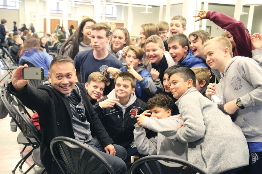 Father Leo Patalinghug and students from St. Margaret School, Rumford, take a selfie in Cathedral Hall following a morning presentation for students of Rhode Island Catholic schools.