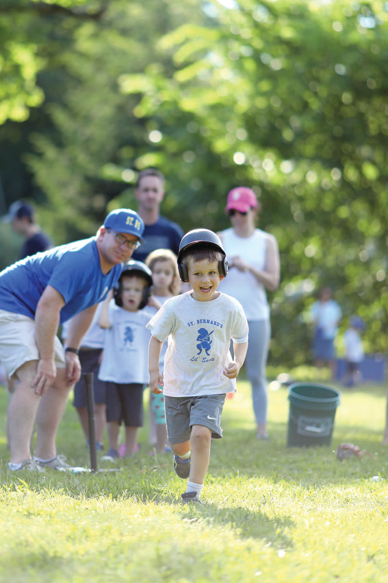 "Coach Ed Cooney, a parishioner at St. Bernard Church in North Kingstown, helps 3 to 6-year-old ""Lil Saints"" learn the basics of baseball at St. Bernard's tee-ball program which ran throughout June."