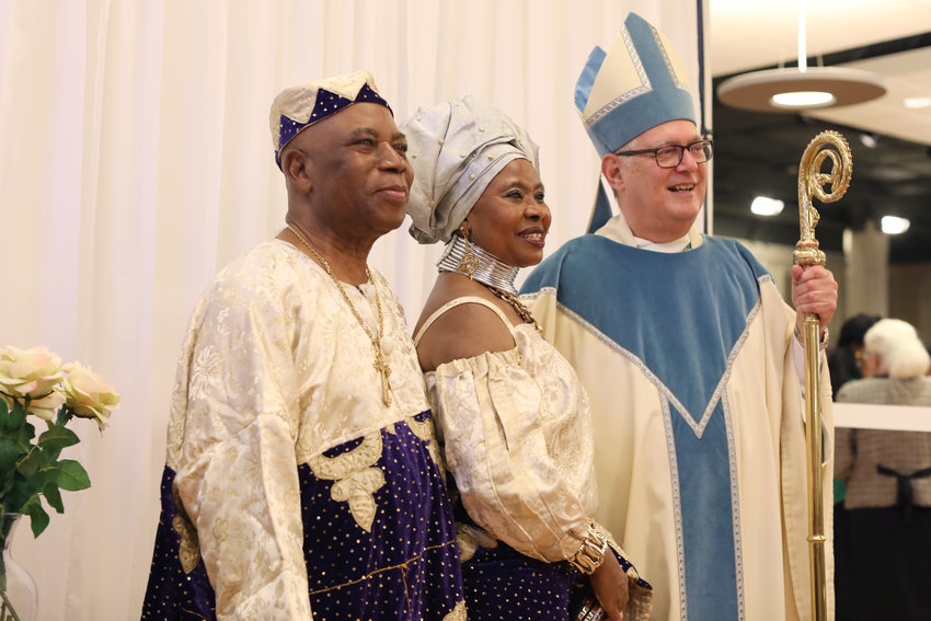 Celebrating 42 years of marriage, Augustina and Paschal Aguocha smile with Bishop Thomas J. Tobin after he offered Mass for couples celebrating wedding anniversaries.