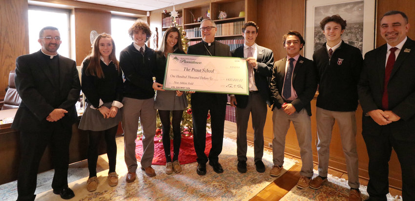 On Tuesday, Dec. 10, students and staff from The Prout School visited with Bishop Thomas J. Tobin at his Chancery office in Providence. The bishop presented them with a check for $100,000 to assist with the cost of a new athletic field on Prout's campus. Pictured from left, Father Carl Fisette, school chaplain; Ellie Edwards; Drew Brouillette; Stella Mayo; Bishop Tobin; Zach Bowe; Colin Bois; Aidan O'Neill; and Dave Estes, principal.