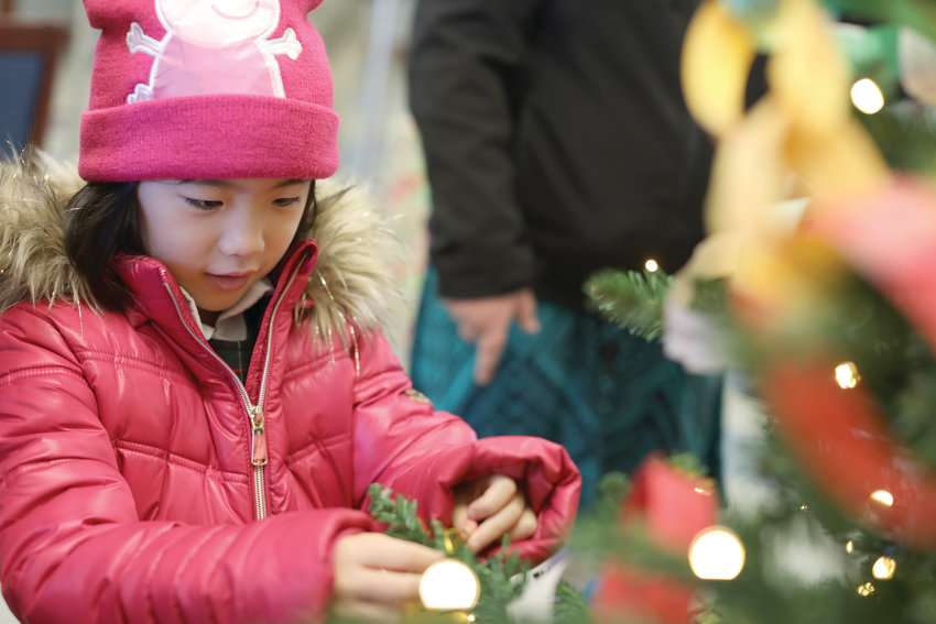 Emily Lim joins her schoolmates in bringing Christmas to the Navigant Park Square Branch, across the street from Msgr. Gadoury Catholic Regional School on Dec. 5.