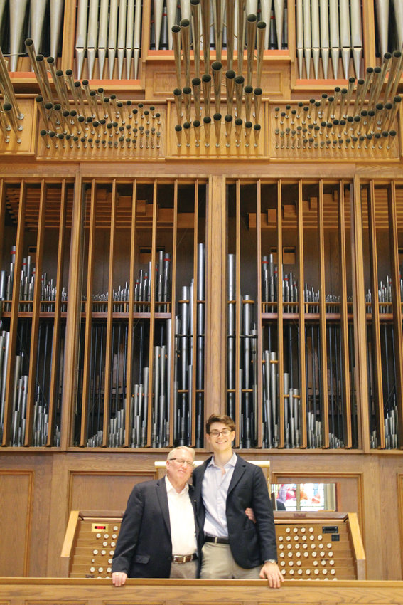 Standing in front of the historic pipe organ at the Cathedral of Saints Peter and Paul, Providence, Nathan Schneider smiles with Phillip Faraone, cathedral organist and Schneider's music and theology teacher from The Prout School.