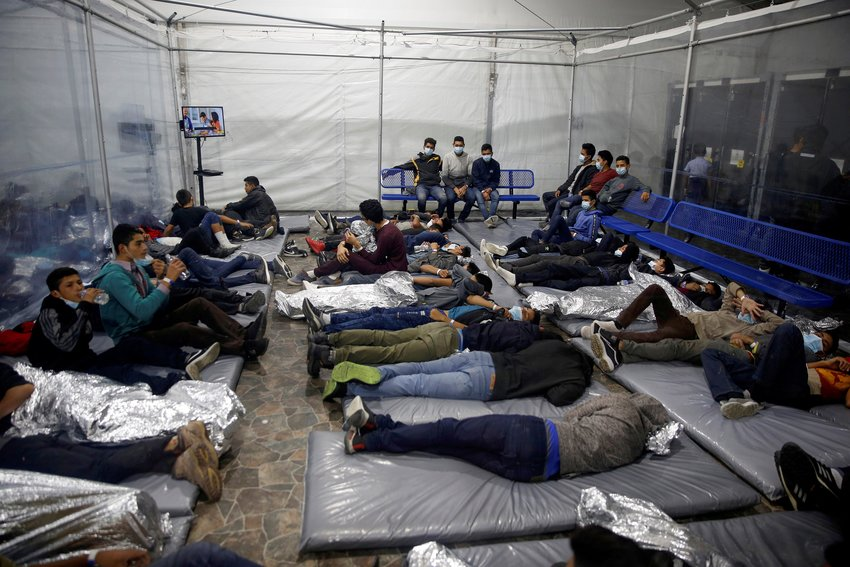 Young migrants lie inside a pod at the Donna Department of Homeland Security holding facility in Donna, Texas, March 30, 2021. (CNS photo/Dario Lopez-Mills, Pool via Reuters)