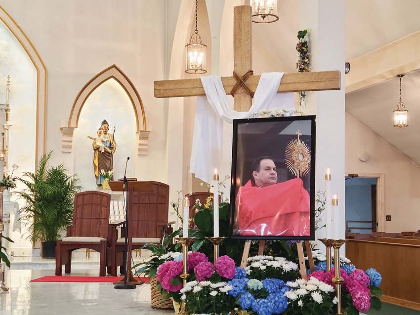 A framed photo of Father Marinaldo Batista in the sanctuary of St. Elizabeth Church in Bristol. Father Batista died from COVID-19 complications in his native Brazil on April 1, Holy Thursday.