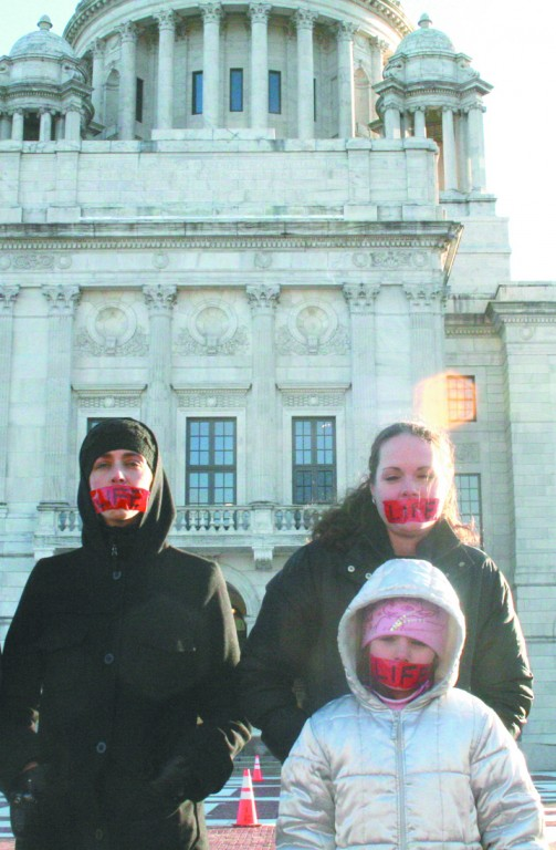 """FOR LIFE: Frank and Connie Joyal and Amelia Heon, front, stand in front of the State House during the rally with red stickers with the word """"Life"""" on their mouths. They are part of a group called Bound 4 Life that recently started a Rhode Island chapter. Their silent protest and the vocal protests inside were part of the annual rally that raises awareness of the pro-life movement and its supporters in the state legislature. Governor Carcieri and his wife, First Lady Sue Carcieri, were among the politicians in attendance. Father Christopher M. Mahar from St. Mary parish in Cranston spoke at the rally."""