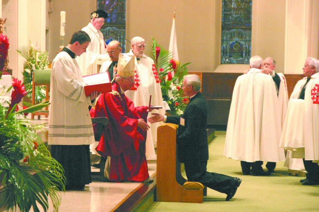 KNIGHTED: Bishop John B. McCormack of Manchester inducts a new member of into the Knights in the Equestrian Order of the Holy Sepulchre of Jerusalem at St. Joseph Cathedral in a ceremony on October 27th.  Both clergy and lay people were inducted into the order during the ceremony, including several Rhode Islanders.