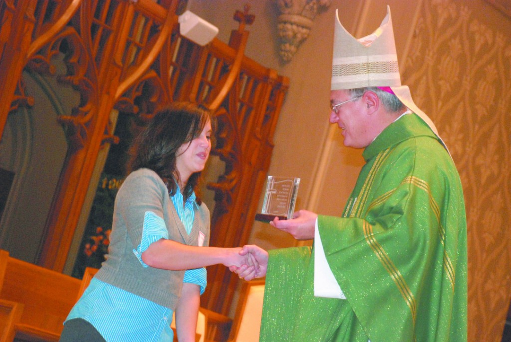 ST. TIMOTHY AWARD:  Ashley Ricard is presented the Saint Timothy Award by Bishop Tobin.  To view more photos from this event, please click on the MyCapture link in the above navigation bar.