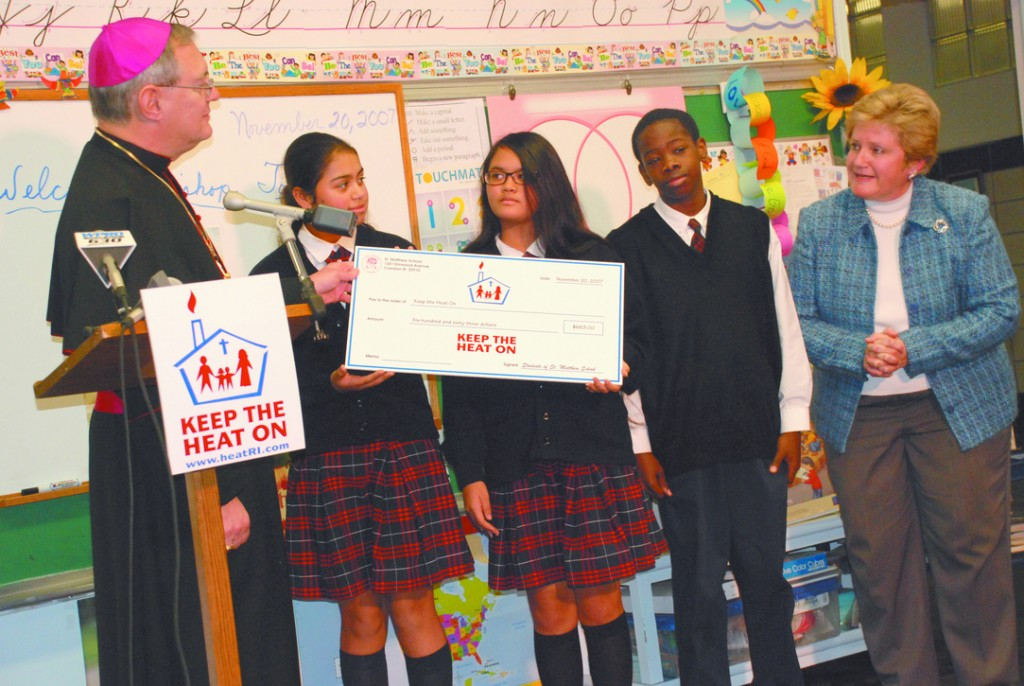 "GENEROUS STEWARDS: Members of the St. Matthew School student council, Cranston, presented a check for $663 to Bishop Thomas J. Tobin on November 20 to kick off the third annual ""Keep the Heat On"" campaign. Standing with the Bishop are students Natalia Ramirez (second from left), Julie Tang and Tunji Omisore and School Principal Elaine P. Dykstra."