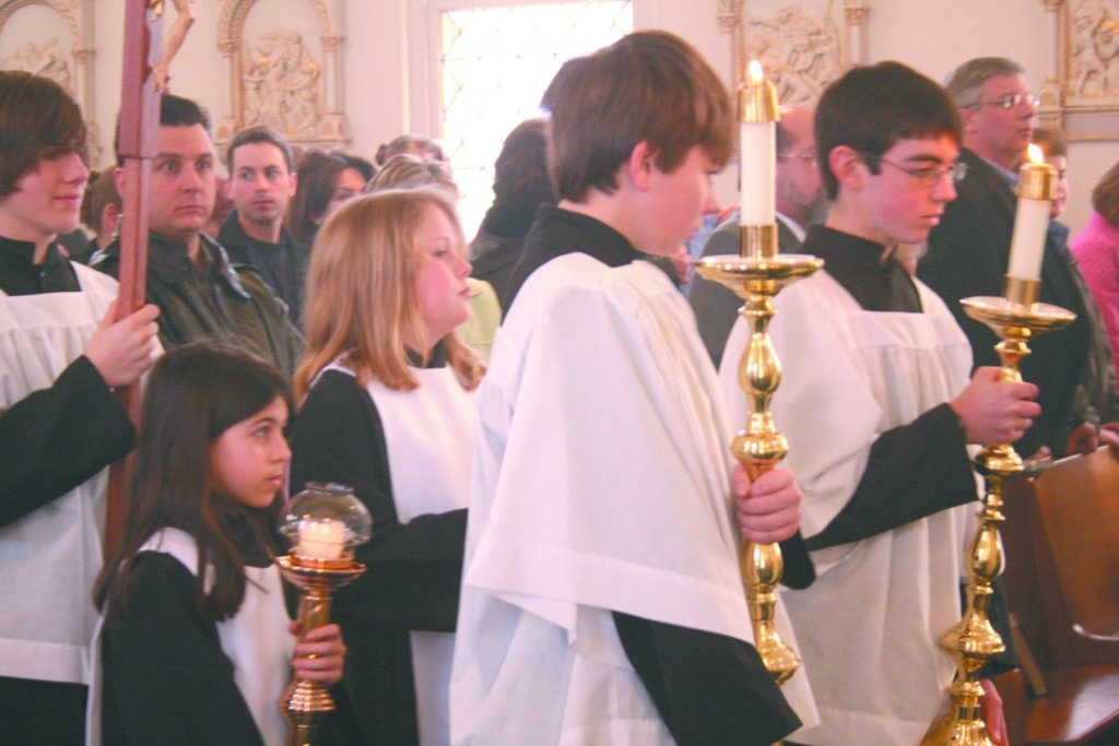 EASTER SUNDAY: Altar servers carry candles and a cross to the altar at Easter Mass at St. Ambrose parish in Albion on Sunday.